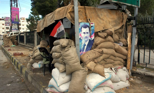 A poster of the Syrian leader at a checkpoint on the outskirts of Damascus. Western governments are considering direct intervention in the wake of gas attacks. Photo: Elizabeth Arrott for Wikimedia Commons.