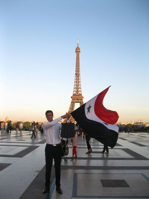 A man displaying the Syrian flag near the Eiffel Tower. Photo: morganmamaria for flickr.
