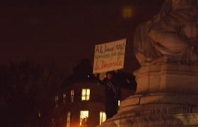 """Man stands on a statue at the Place de la République with a sign that reads: """"We answer to terror through more democracy"""". Photo: Hugo Argenton for La Jeune Poltique."""