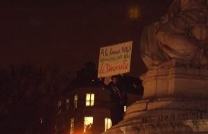 "Man stands on a statue at the Place de la République with a sign that reads: ""We answer to terror through more democracy"". Photo: Hugo Argenton for La Jeune Poltique."
